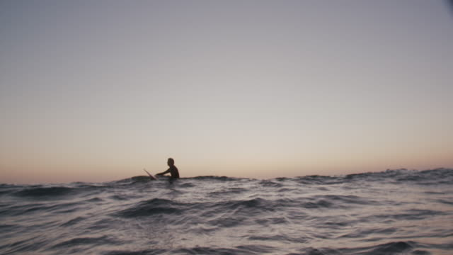 young man surfing at sunset - auf dem bauch liegen stock-videos und b-roll-filmmaterial