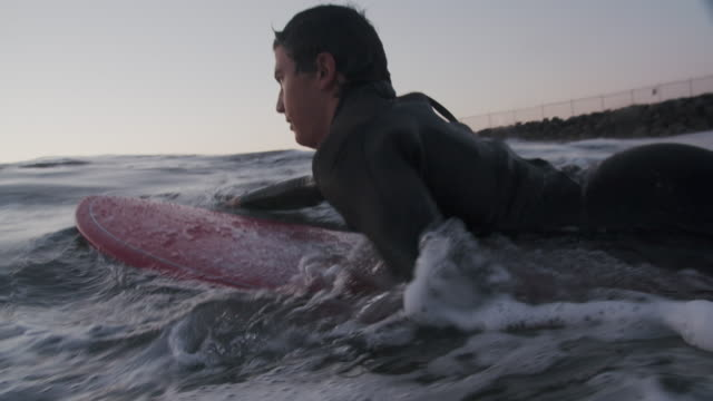 cu young man surfing at sunset - lying on front stock videos & royalty-free footage