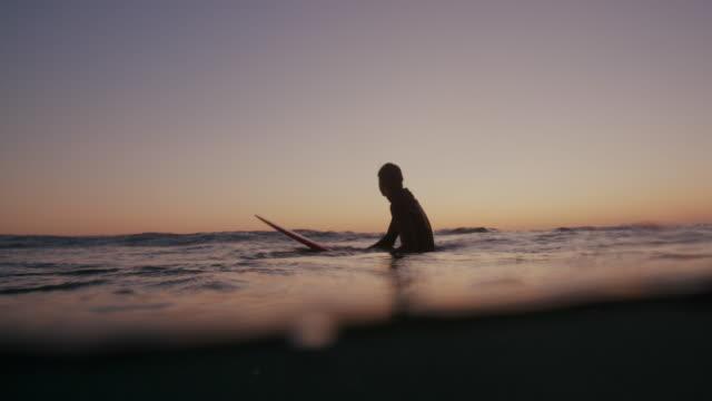 sm young man surfing at sunset - surfbräda bildbanksvideor och videomaterial från bakom kulisserna