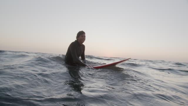 vídeos de stock e filmes b-roll de sm young man surfing at sunset - rebentação