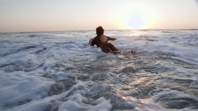 young man surfing at sunset - using a paddle stock videos & royalty-free footage