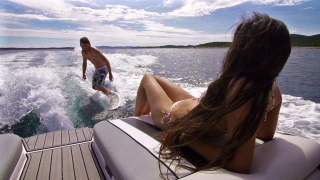 young man surfing behind a boat, woman sunbathing - skimboarding stock videos & royalty-free footage