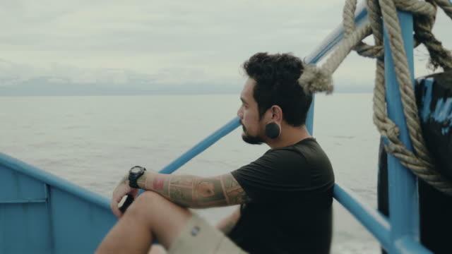 junger mann mit smartphone in thai taxi-boot net surfen - einzelner mann über 30 stock-videos und b-roll-filmmaterial