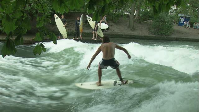 MS Young man surfing on Eisbach river in Englischer Garten (English Garden), Munich, Bavaria, Germany