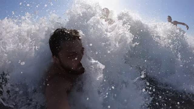 junger mann überrascht von einer großen welle im ozean - augen geschlossen stock-videos und b-roll-filmmaterial
