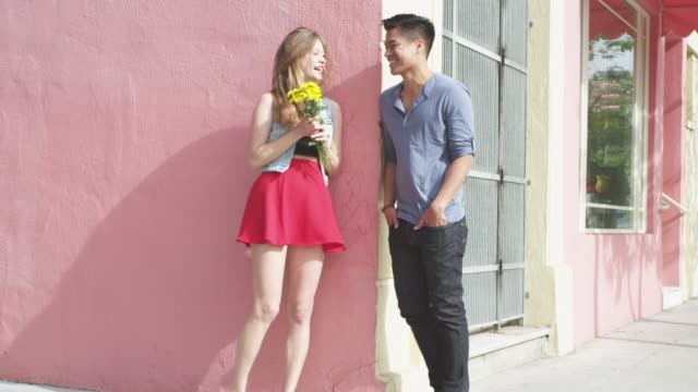 Young man surprises woman with yellow flowers