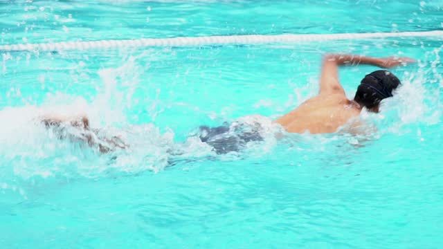 young man swimming freestyle in a race. - length stock videos & royalty-free footage