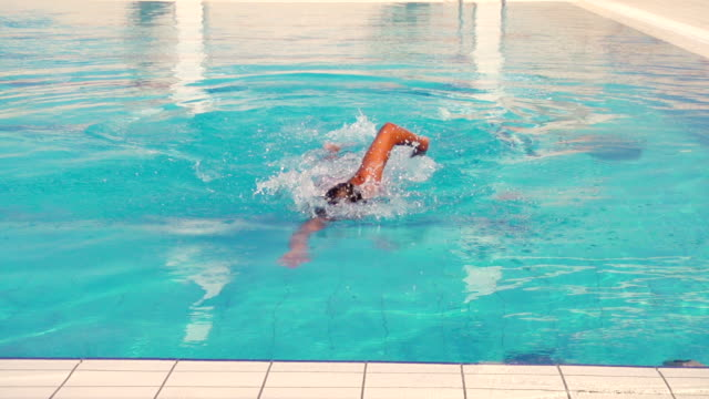 stockvideo's en b-roll-footage met young man swimming front crawl in the pool - buitenbad