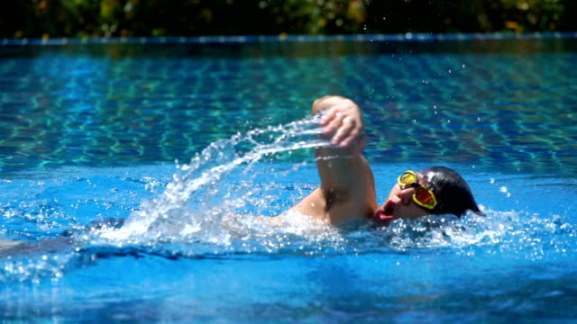 slo mo - young man swimming front crawl - swimming goggles stock videos & royalty-free footage