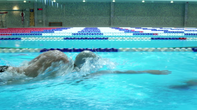 Young man swimming in a swimming pool by himself