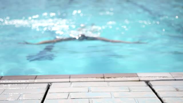 Young man swimming in swimming pool