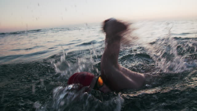 cu ts sm young man swimming in the ocean at dusk - sports training stock videos & royalty-free footage