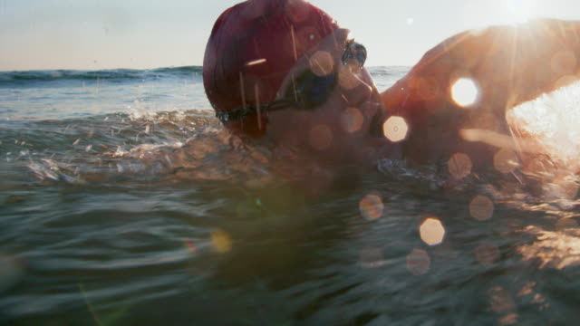 cu sm young man swimming in the ocean at sunset - swimming stock videos & royalty-free footage