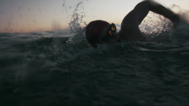cu young man swimming in the sea at dusk - triathlon stock videos & royalty-free footage