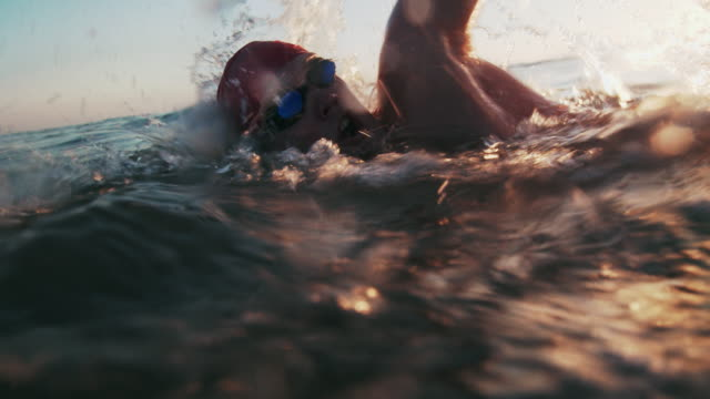 ts sm young man swimming in the sea at sunset - triathlon stock videos & royalty-free footage