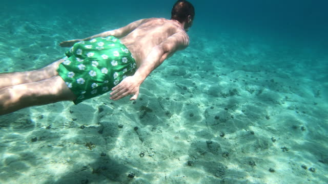 young man swimming underwater in mediterranean sea - swimming trunks stock videos & royalty-free footage