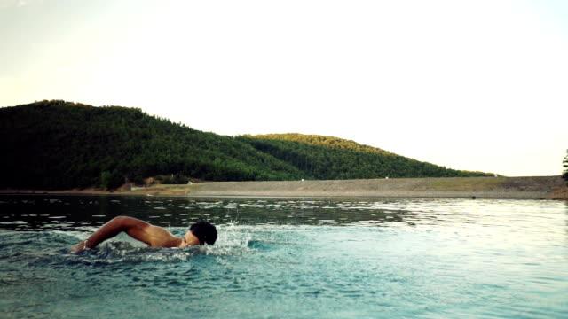 vídeos de stock, filmes e b-roll de jovem rapaz de natação - lago