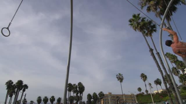 vídeos y material grabado en eventos de stock de a young man swinging on the traveling rings at santa monica beach.  - slow motion - sólo hombres jóvenes