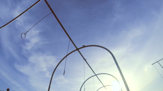 A young man swinging on the traveling rings at Santa Monica beach. - Slow Motion