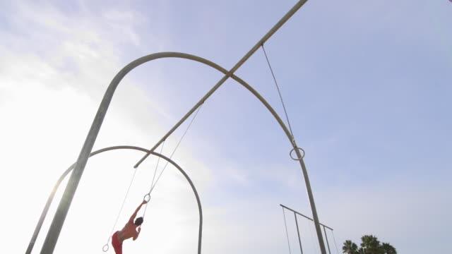 vídeos y material grabado en eventos de stock de a young man swinging on the traveling rings at santa monica beach.  - sólo hombres jóvenes