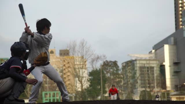 young man swings bat at pitch in baseball - japan - 野球点の映像素材/bロール