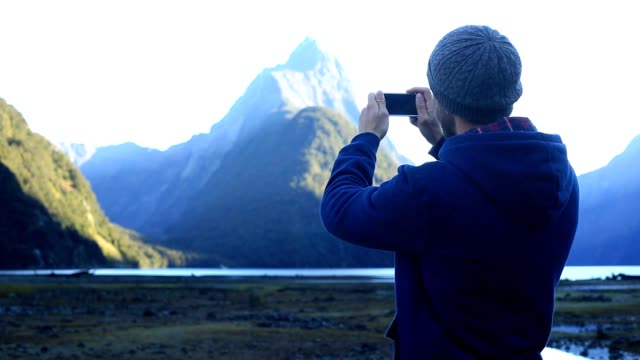 Young man takes a picture of a spectacular mountain landscape with a smart phone