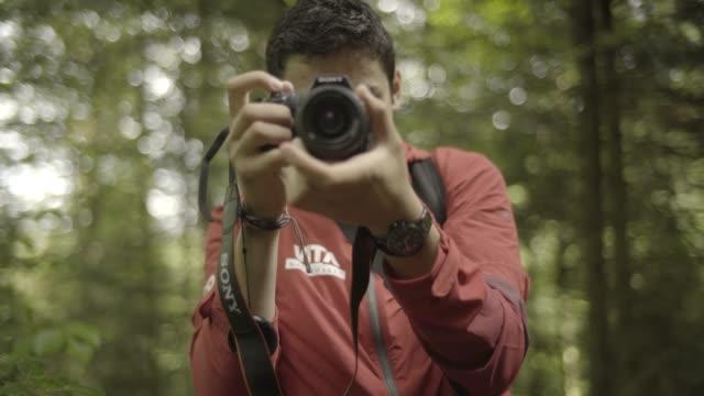 ung man tar dslr foto i skogen - digital spegelreflexkamera bildbanksvideor och videomaterial från bakom kulisserna