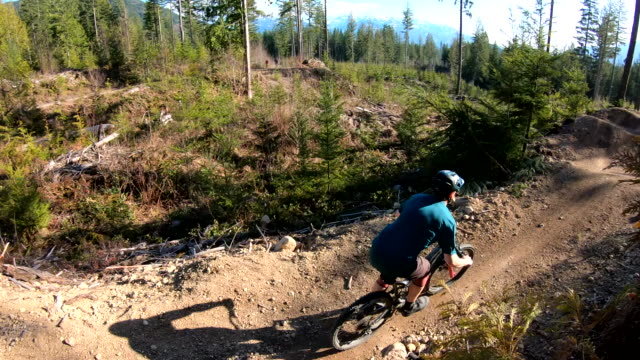 young man takes jumps on mountain bike, along trail - solo uomini giovani video stock e b–roll