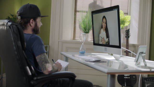 vidéos et rushes de young man takes notes while video conferencing with a colleague. - hot desking