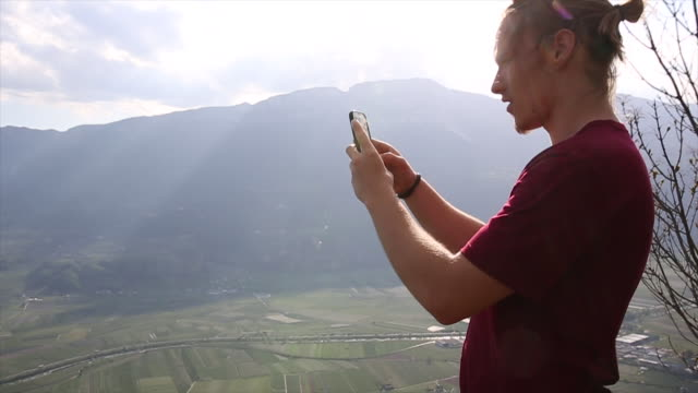 Young man takes pic from mountain view, from castle rampart