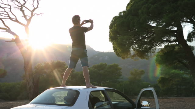 Young man takes picture while standing on car roof