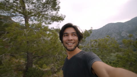young man takes selfie on top of seaside mountain - olympos turkey - panoramic stock videos & royalty-free footage