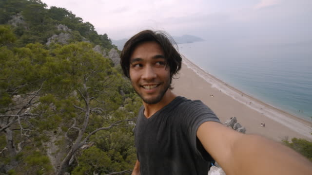 vidéos et rushes de young man takes selfie on top of seaside mountain - olympos turkey - cadrage à la taille