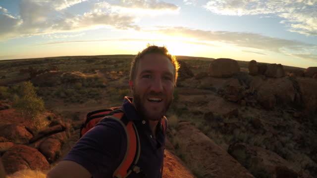 Jonge man neemt selfie portret met spectaculaire landschap bij zonsopgang - 4K