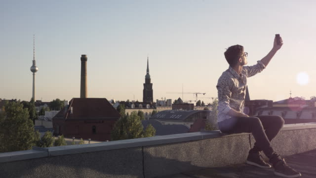 young man takes selfies on a rooftop - one man only stock-videos und b-roll-filmmaterial