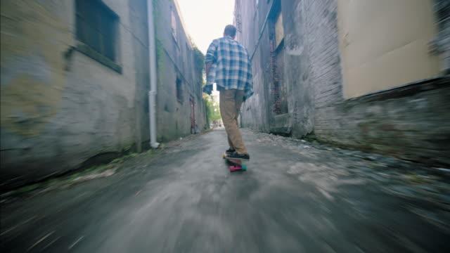 vídeos y material grabado en eventos de stock de young man takes shortcut through downtown alley on skateboard - patinaje en tabla larga