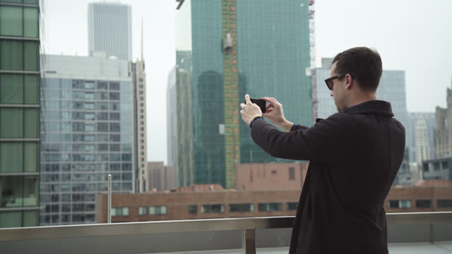 young man takes smartphone photos of chicago skyscrapers from balcony of high rise. - photography stock-videos und b-roll-filmmaterial