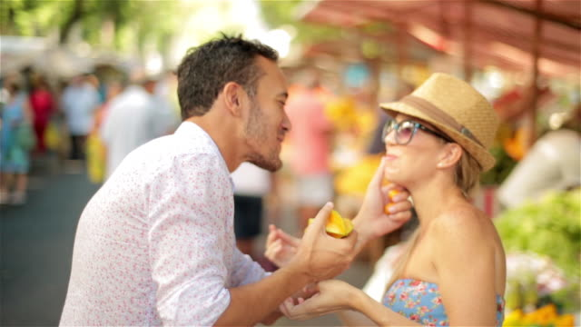 young man takes starfruit and wipes juice from girlfriend's mouth in brazilian marketplace - mercato di prodotti agricoli video stock e b–roll