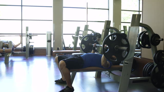 young man taking a break from weightlifting in a gym - bench press stock videos & royalty-free footage