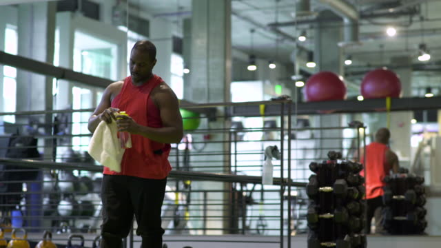 vídeos de stock e filmes b-roll de young man taking a break in a gym - só um homem de idade mediana
