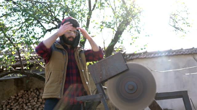 vídeos y material grabado en eventos de stock de joven tomando un descanso al aserrar en el patio trasero - masculinidad