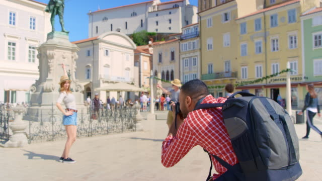 young man taking a photo of his girlfriend in a town square - slovenia stock videos & royalty-free footage
