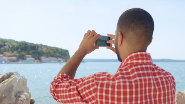 Young man taking a photo of the town by the sea with his smartphone on a sunny day