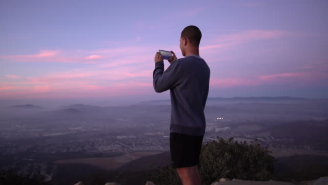 ws young man taking a photo of the view - photographing stock videos and b-roll footage