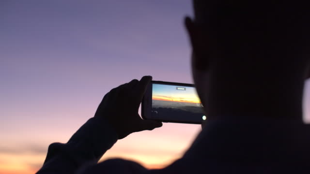 cu rv young man taking a photo with his phone at sunset - photography video stock e b–roll