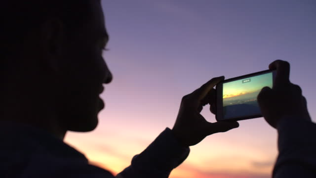 cu young man taking a photo with his phone - photography stock videos & royalty-free footage