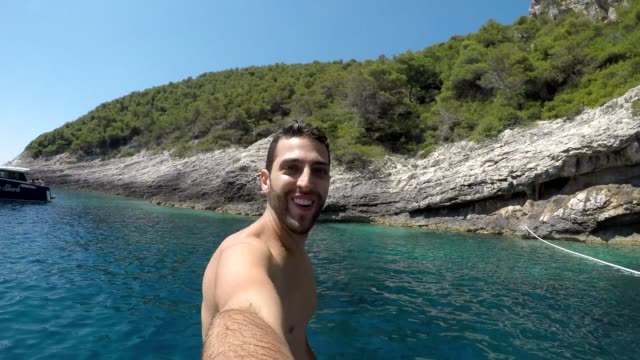young man taking a selfie jumping at hvar coastline, croatia - selfie video stock e b–roll