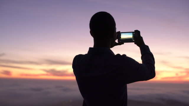 ms rv young man taking a video at sunset - photo shooting stock videos and b-roll footage