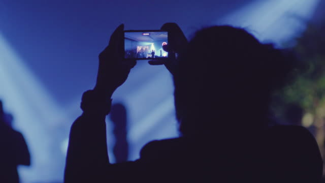 Young man taking a video on concert