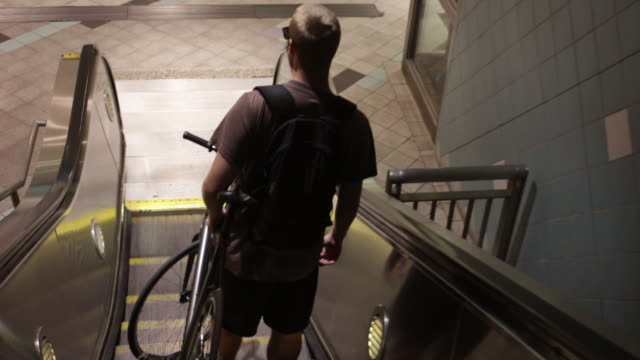 A young man taking an escalator down to the metro station while holding his bike.